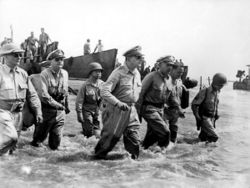 Gen. Douglas MacArthur wades ashore during initial landings at Leyte, Philippine Islands
